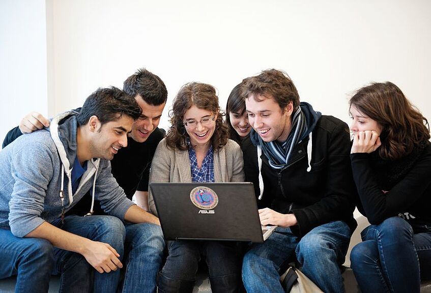 Group of students looks into a laptop.