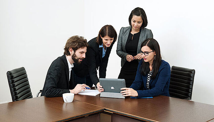 Four people gathering around a laptop.