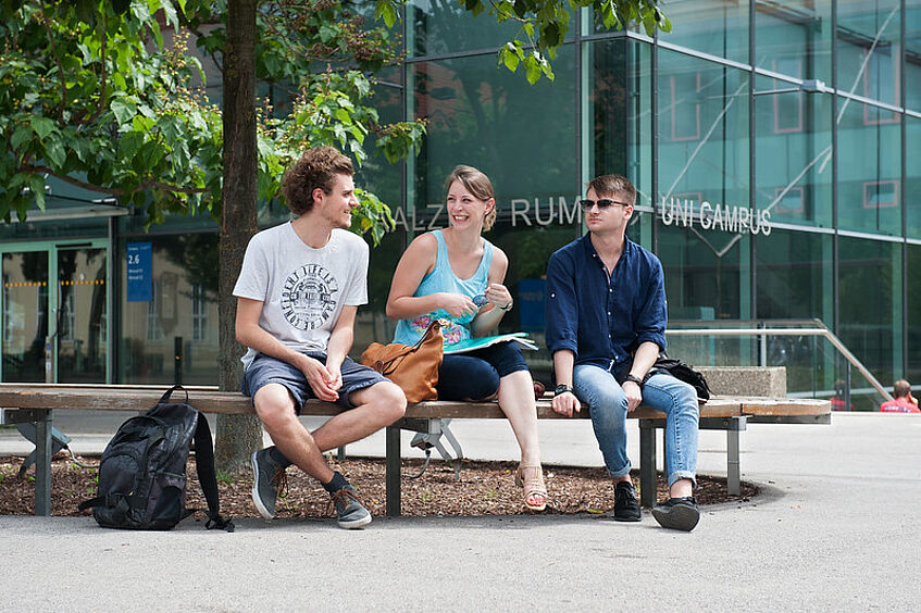 Students sitting in front of the lecture halls at the Campus.