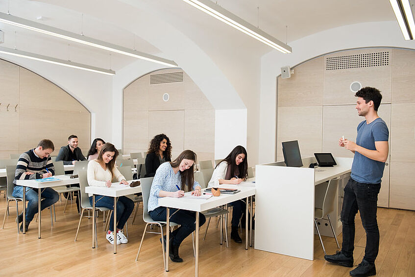 Teacher talking in front of students in a course.